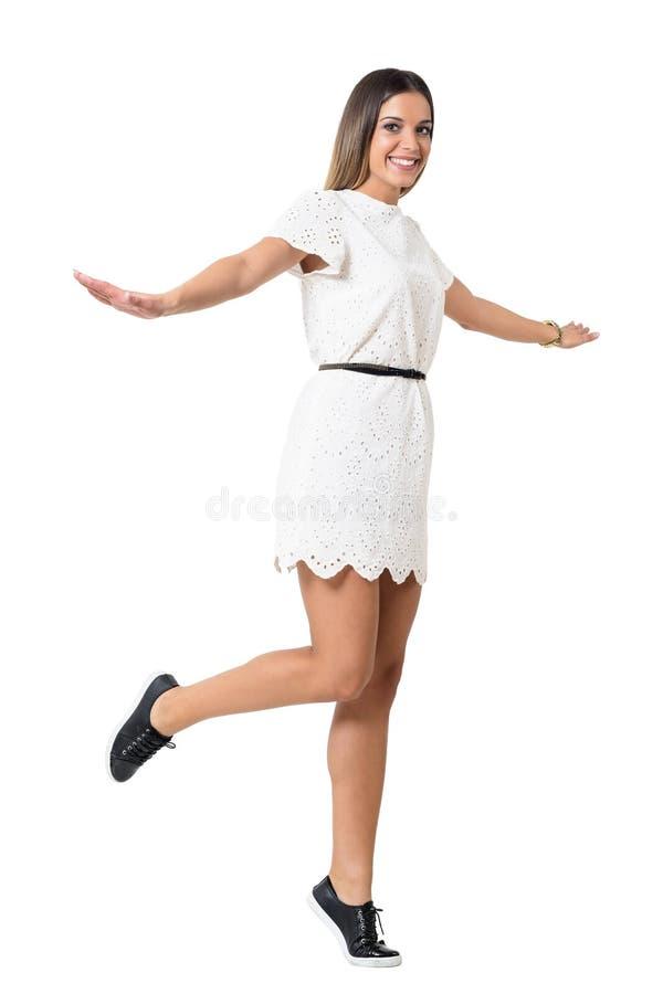 Den lyckliga unga kvinnan snör åt in tvärt klänningbanhoppning i luften som ler på kameran royaltyfri bild