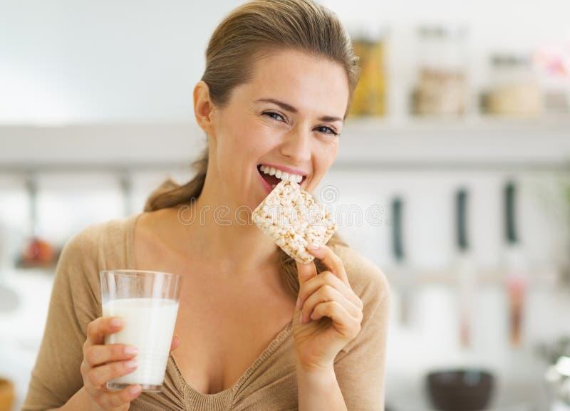 Den lyckliga unga kvinnan som äter knaprigt bröd med, mjölkar i kök fotografering för bildbyråer
