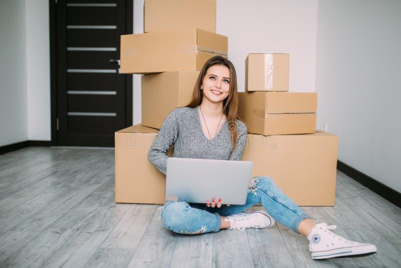 Den lyckliga unga kvinnan som flyttar sig till nytt hem- sammanträde på golvet och bruksbärbara datorn nära, boxas royaltyfri bild