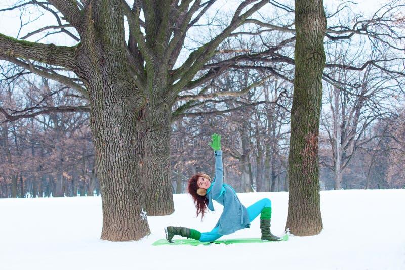 Den lyckliga unga kvinnan som gör yoga på insnöat, parkerar arkivfoton