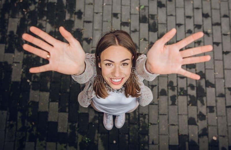Den lyckliga unga kvinnan som lyfter henne händer, up utomhus royaltyfri fotografi