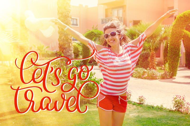 Den lyckliga unga kvinnan som lyfter hennes händer i sommaren, parkerar, och text Lets går loppet Attraktion för kalligrafibokstä fotografering för bildbyråer