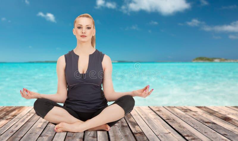 Den lyckliga unga kvinnan som mediterar i yogalotusblomma, poserar arkivfoto