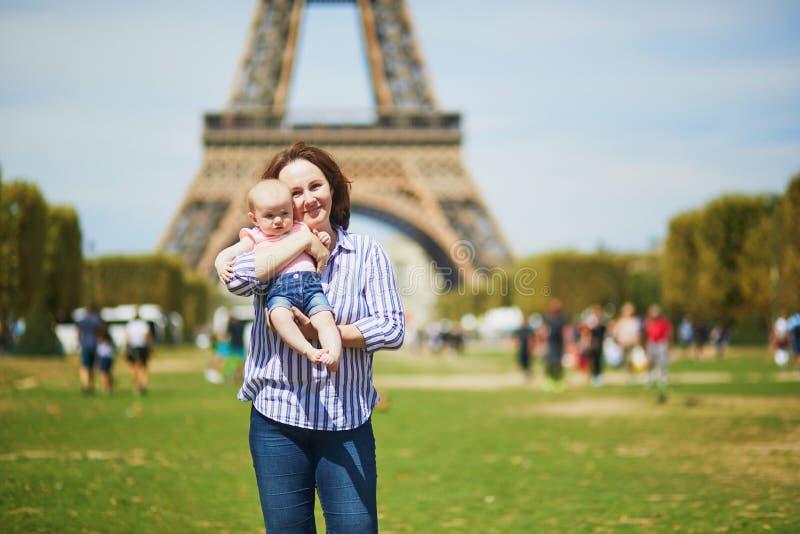 Den lyckliga unga kvinnan som rymmer hennes litet, behandla som ett barn flickan i Paris royaltyfri foto
