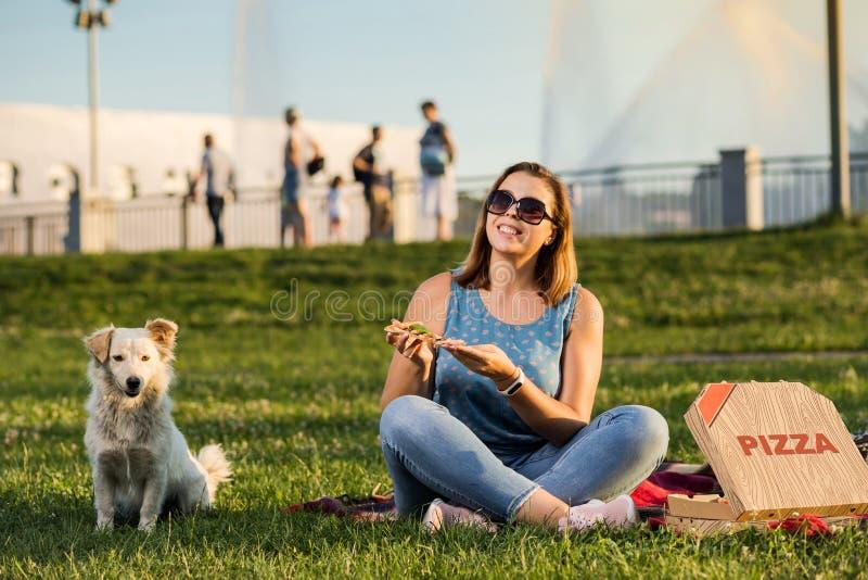 Den lyckliga unga kvinnan som rymmer varm pizza i ask, placerar utomhus- parkerar in arkivfoton