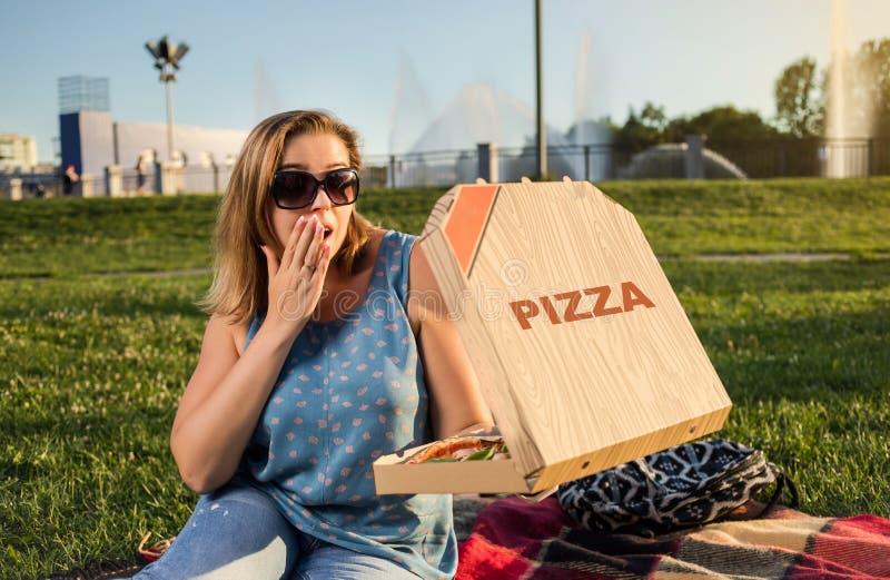 Den lyckliga unga kvinnan som rymmer varm pizza i ask, placerar utomhus- parkerar in royaltyfria bilder