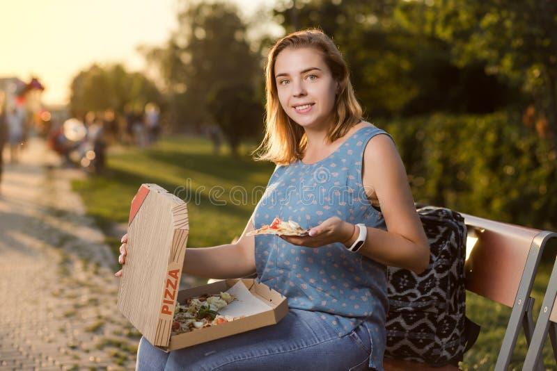 Den lyckliga unga kvinnan som rymmer varm pizza i ask, placerar utomhus- parkerar in arkivfoto