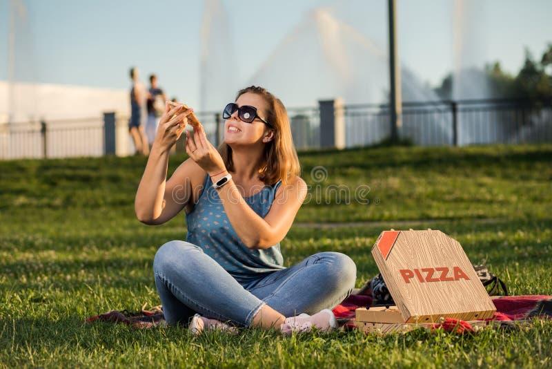 Den lyckliga unga kvinnan som rymmer varm pizza i ask, placerar utomhus- parkerar in royaltyfri bild