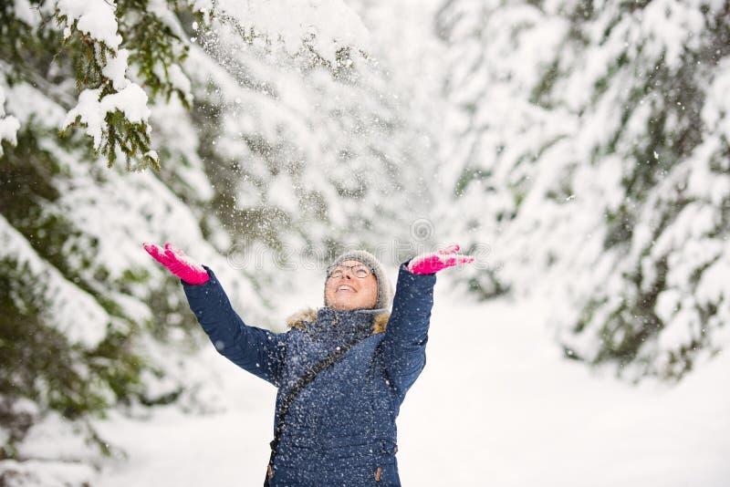 Den lyckliga unga kvinnan spelar med en insnöad solig vinterdag royaltyfri bild