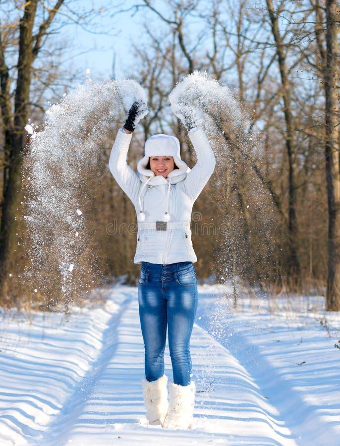 Den lyckliga unga kvinnan spelar med en insnöad vinter royaltyfri bild