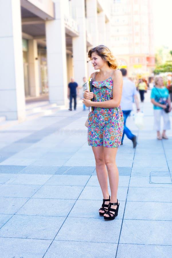 Den lyckliga unga kvinnan, student går gatorna av en storstad arkivbilder