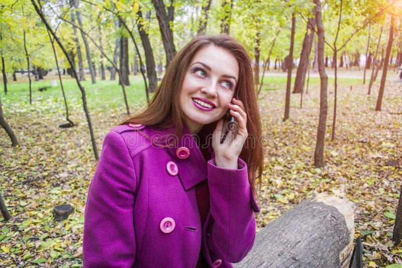 Den lyckliga unga kvinnan talar på en smartphone i hösten parkerar royaltyfri fotografi