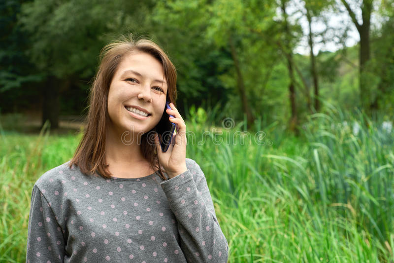 Den lyckliga unga kvinnan talar på telefonen i skogen royaltyfri bild