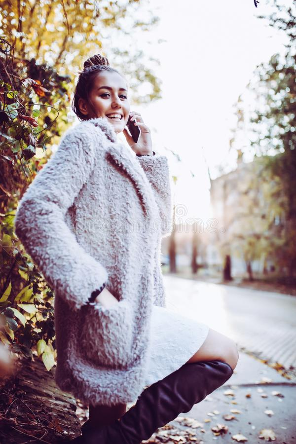 Den lyckliga unga kvinnan talar vid telefonen på gatan royaltyfri foto