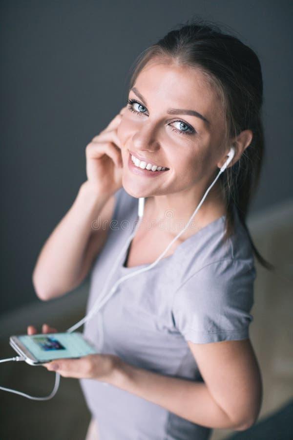 Den lyckliga unga le kvinnan i hörlurar lyssnar till musik med den smarta telefonen royaltyfri bild
