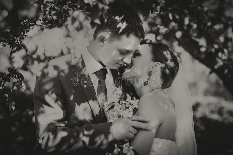 Den lyckliga unga maken och frun, i blommor, ser de buketten Svart vitt fotografi fotografering för bildbyråer