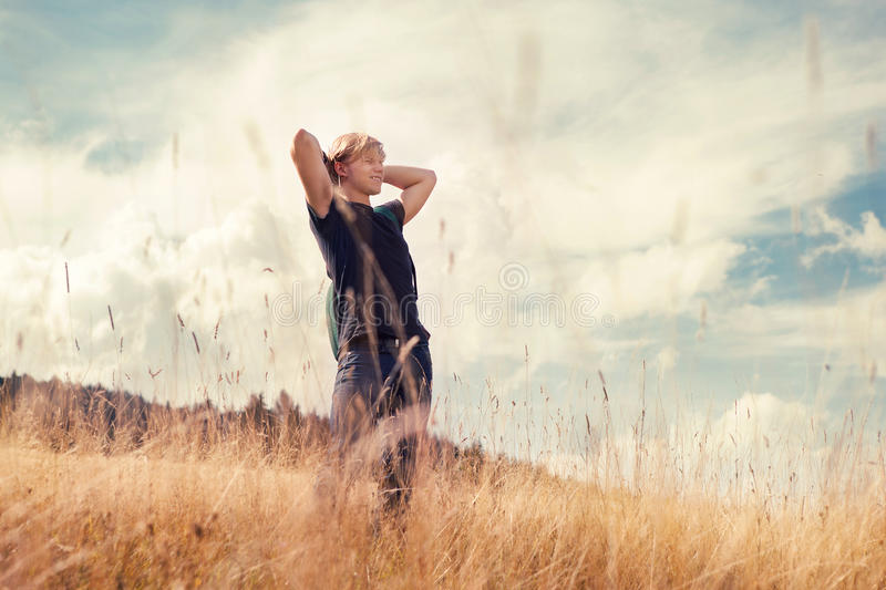 Den lyckliga unga mannen går på guld- höstfält royaltyfri bild