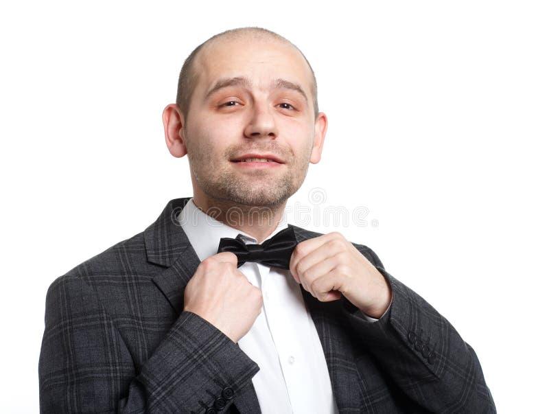 Den lyckliga unga mannen justerar hans fluga arkivfoton