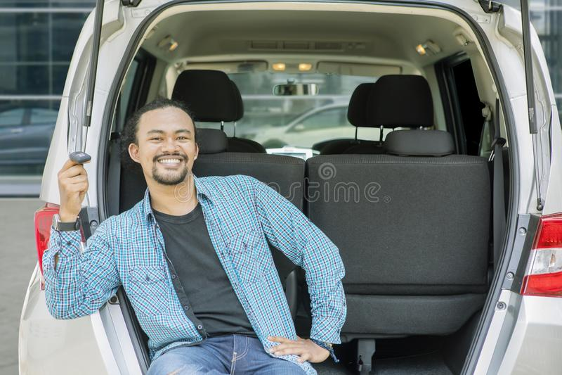 Den lyckliga unga mannen rymmer en biltangent i bilstammen royaltyfri foto