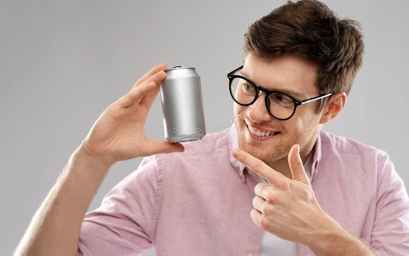 Den lyckliga unga mannen som rymmer tenn kan med sodavatten royaltyfria foton