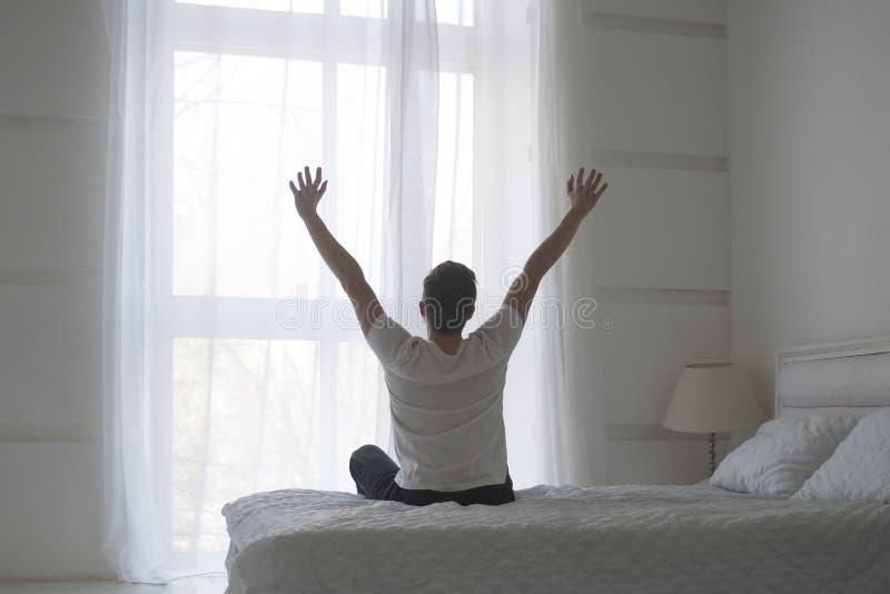 Den lyckliga unga mannen som sträcker i säng, når han har vaknat upp, beskådar tillbaka royaltyfri bild