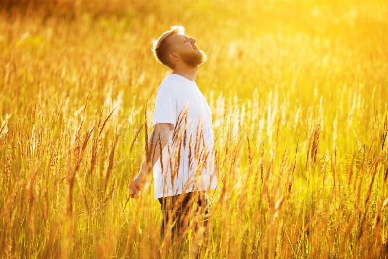 Den lyckliga unga mannen står i fältet arkivbild