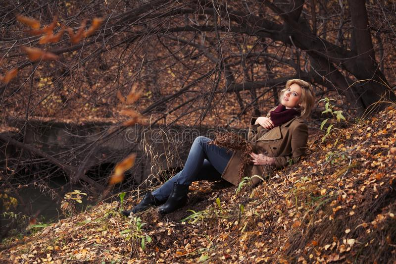 Den lyckliga unga modekvinnan som sitter på jordning i höst, parkerar royaltyfri foto