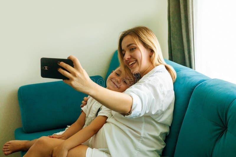 Den lyckliga unga modern gör selfiefotoet med hennes son fotografering för bildbyråer
