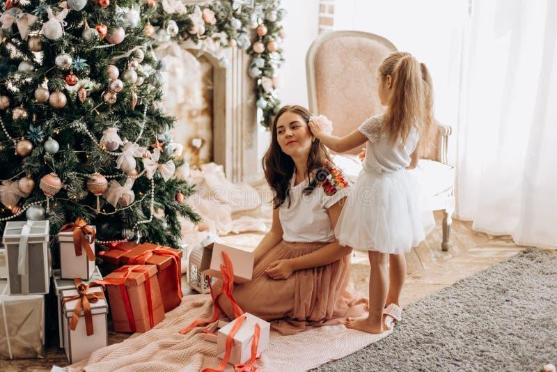 Den lyckliga unga modern och hennes lilla dotter i trevlig klänning sitter ne fotografering för bildbyråer