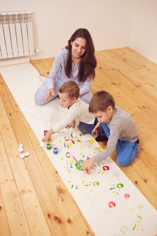 Den lyckliga unga modern och hennes två iklädda hem- kläder för små söner sitter på trägolvet i rummet och royaltyfria bilder