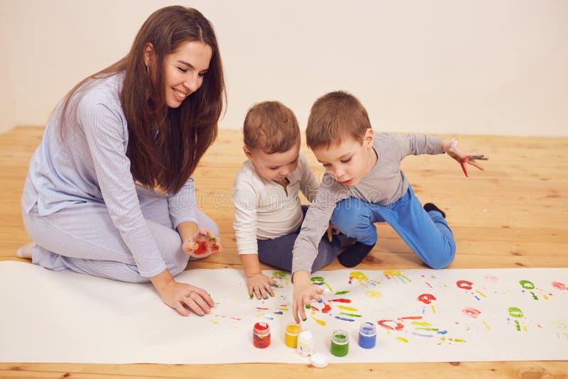 Den lyckliga unga modern och hennes tv? ikl?dda hem- kl?der f?r sm? s?ner sitter p? tr?golvet i rummet och fotografering för bildbyråer