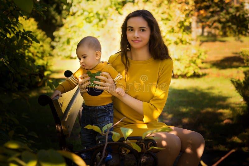 Den lyckliga unga modern som spelar med, behandla som ett barn i höst parkerar med gula lönnlöv Familj som utomhus går i höst Pys arkivfoton