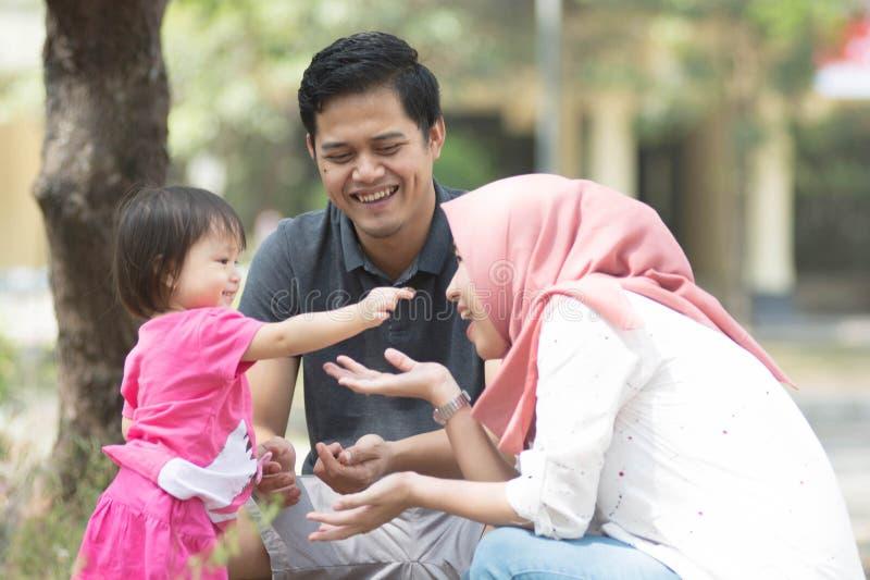 Den lyckliga unga muslim familjen som spelar på, parkerar med lilla flickan som visar något till hennes mamma i bärare på den sol arkivbilder
