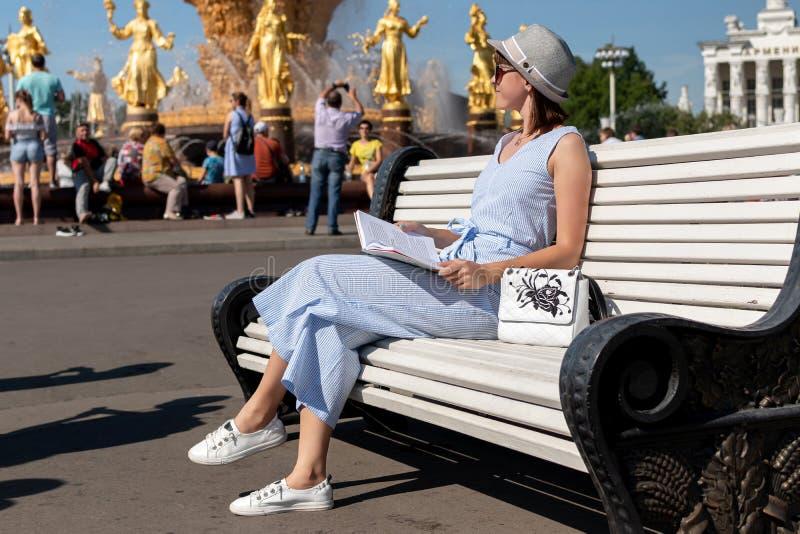 Den lyckliga unga och stilfulla kvinnan med hatten och boken som sitter på bänken i, parkerar royaltyfri bild