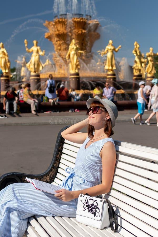 Den lyckliga unga och stilfulla kvinnan med hatten och boken som sitter på bänken i, parkerar royaltyfri fotografi