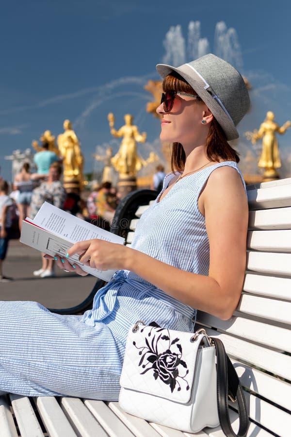 Den lyckliga unga och stilfulla kvinnan med hatten och boken som sitter på bänken i, parkerar fotografering för bildbyråer