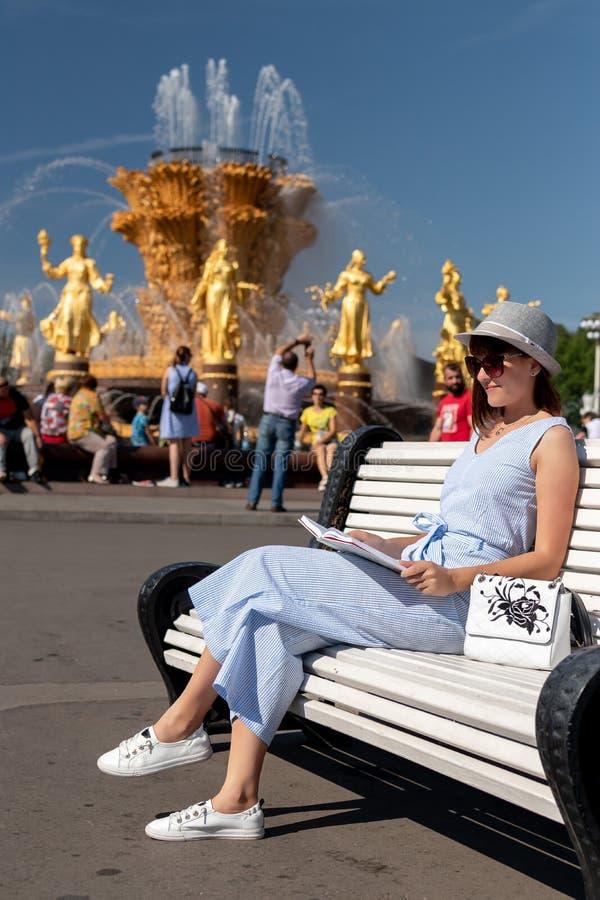 Den lyckliga unga och stilfulla kvinnan med hatten och boken som sitter på bänken i, parkerar royaltyfri foto