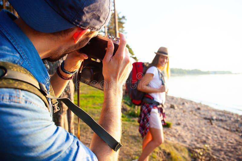 Den lyckliga unga parhandelsresanden med ryggsäcken tar fotoet på skogen, lopp och fotvandrabegrepp royaltyfria foton