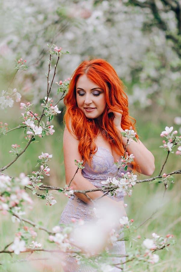 Den lyckliga unga rödhåriga kvinnan står, i att blomstra upp äpplefruktträdgården, slut arkivbilder