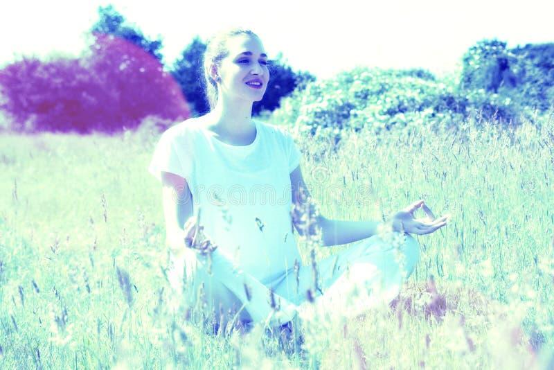Den lyckliga unga yogakvinnan för energi och anda övar utanför royaltyfria foton
