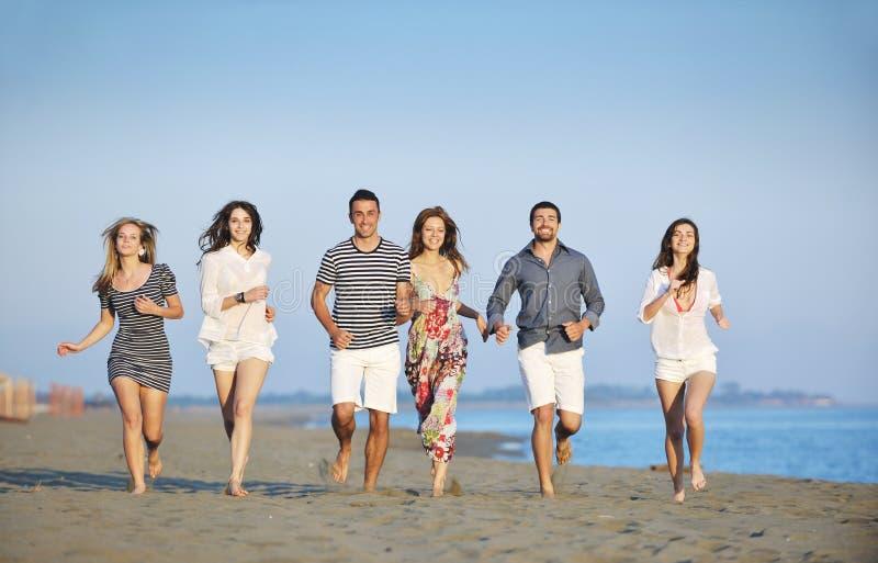 Den lyckliga ungdomaren grupp har gyckel på strand royaltyfria foton