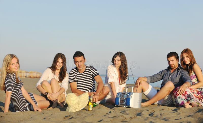 Den lyckliga ungdomaren grupp har gyckel på strand fotografering för bildbyråer