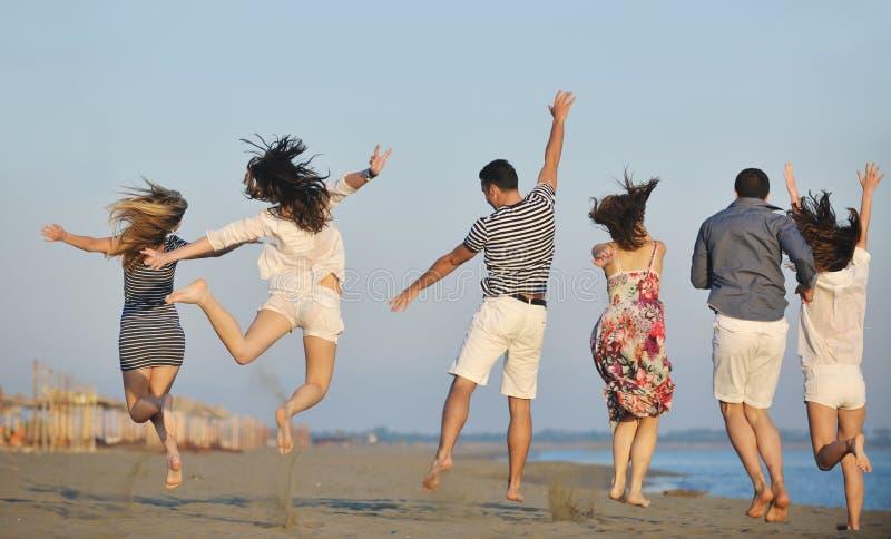 Den lyckliga ungdomaren grupp har gyckel på strand arkivbild