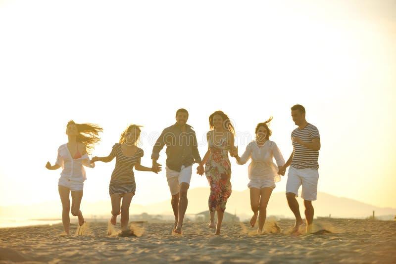 Den lyckliga ungdomaren grupp har gyckel på strand royaltyfri fotografi