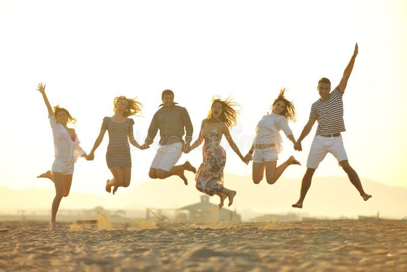 Den lyckliga ungdomaren grupp har gyckel på strand royaltyfri bild