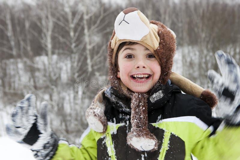 Den lyckliga ungen leker lite i snow arkivbilder