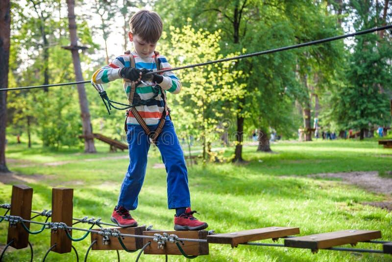 Den lyckliga ungen som spelar på affärsföretaget, parkerar, rymmer rep och klättrar trätrappa royaltyfria foton