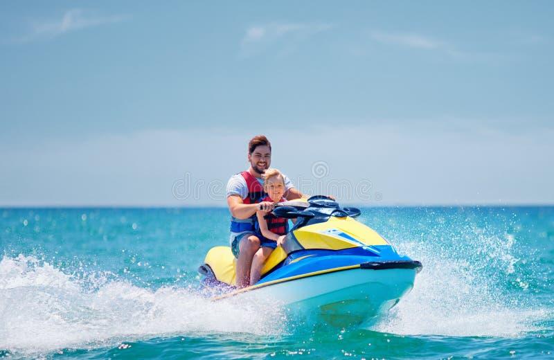 Den lyckliga upphetsade familjen, fadern och sonen som har gyckel på strålen, skidar på sommarsemestern arkivfoton