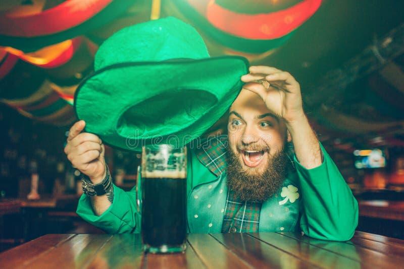 Den lyckliga upphetsade unga mannen i grön dräkt sitter på tabellen i bar Han rymmer hatten över rånar av mörkt öl Leende för ung royaltyfri foto