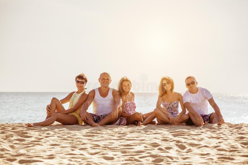 Den lyckliga vänfamiljstranden semestrar begrepp royaltyfria foton